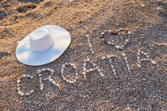 Stone inscription with hat on the pebbles Stock Image