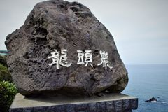 Stone with the inscription of Yongduam Rock, Dragon Head Rock in Jeju, Korea royalty free stock image