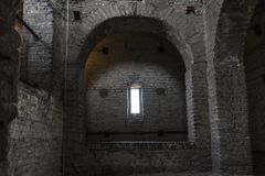Dark crypt with rectangular window. Stone interior with window of an old steeple crypt, located inside an ancient catholic church royalty free stock photos