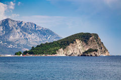 Stone island with green forest at sea near high mountain Stock Images