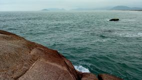 Stone and island in the sea of Florianópolis royalty free stock photography
