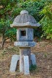 Japanese garden lantern. Stone Japanese garden lantern in the garden Royalty Free Stock Images