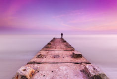 Stone jetty and calm seas. A concrete and stone jetty reaches out to the sunset sky through calm seas on Bournemouth Beach. The jetty is a favourite place for Royalty Free Stock Photography