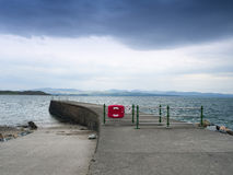 Stone jetty with life buoy in Criccieth Gwynedd Wales UK Royalty Free Stock Photo