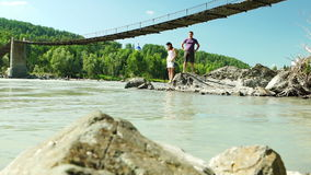 Stone in Katun river and old suspension bridge stock footage