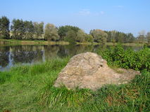 A stone at the lake. A stone on the bank of a lake stock photography