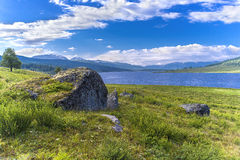 Stone on lake. Magnificent landscape with a kind on lake and snow mountains, with a stone in the foreground Stock Photos