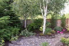 Stone Landscaping. A custom designed dry creek is a feature of this perennial backyard garden Royalty Free Stock Photos