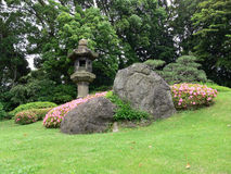 Stone lantern. Arrangement with a stone lantern, rocks and flowers in a japanese park stock image