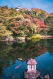 Stone lantern at Koko-en Garden in Himeji, Japan. A small stone lantern in the lake at Koko-en Garden in autumn, with Himeji Castle rooftop just showing over stock images