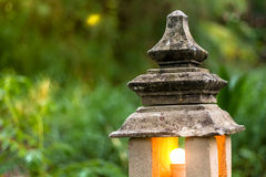Stone lantern lamp with light bulb inside in the green garden forest environment Stock Photo