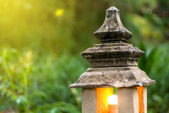 Stone lantern lamp with light bulb inside in the green garden forest environment Stock Image