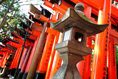 Stone lantern with torii Royalty Free Stock Photo