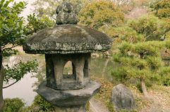 Stone lantern in zen garden. Ancient stone lantern in traditional Japanese zen garden in Kyoto, Japan; focus on lantern Stock Image