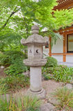 Stone lantern in Zojo-ji Temple, Tokyo, Japan. Traditional stone lantern (toro) in the garden of Zojo-ji Temple in Tokyo, Japan. Lit lanterns are considered an Stock Photo