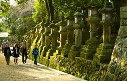 Stone lanterns tourists Kasuga Taisha Shrine Nara. Tourists visiting ancient stone lanterns with moss on them in Kasuga Taisha shrine, Nara, Japan Royalty Free Stock Images