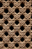 Stone Latticework with Flowers Pattern. Carved stone latticework with flowers and squares design creating a perforated wall Royalty Free Stock Image