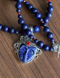 Stone lazuli necklace. Precious natural stone colour beads red crystals faseted and blue lapis lazuli and silver pendant whis carved face royalty free stock images