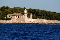 Stone light house in Mali Losinj,Croatia. Stone made light house in Mali Losinj with the pine forest in background Royalty Free Stock Image
