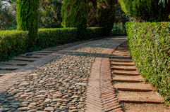 Stone-lined walkway in the park. Stone-lined walkway in the mediterranian park with bright greenery Royalty Free Stock Photo