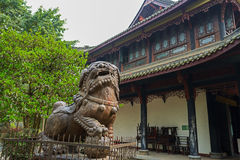 Stone lion before ancient building,Chengdu. The aged stone statue of a male lion stands in front of an ancient Chinese traditional wood structure building Stock Images