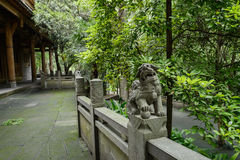 Stone lion on balustrade along lichen-covered path before ancien Royalty Free Stock Image