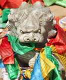 Stone lion figure with traditional buddhist prayer flags Stock Images