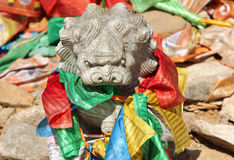 Stone lion figure with traditional buddhist prayer flags Royalty Free Stock Photo