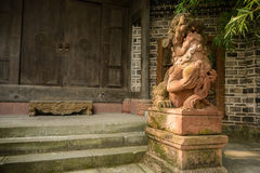 Stone lion at gate of ancient Chinese mansion on sunny day Royalty Free Stock Photo