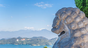 Stone lion looking out over Sun Moon Lake in Taiwan. Stone lion looking out over Sun Moon Lake from the Wenwu temple in Taiwan Stock Photos