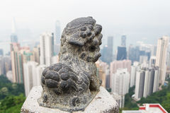 Stone lion statues and the city. Stone lion statues and blurred city view of Hong Kong stock images