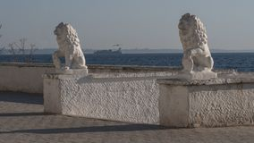 Two stone lion statues on the seafront in Odesa. Stone lion statues on the seafront in Odesa, Ukraine. Opposite coast of the bay and a cargo ship visible in the royalty free stock photos
