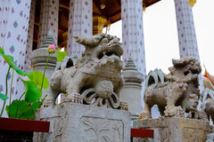 Stone lion Thai-Chinese sculpture in Wat Arun buddhist temple in Bangkok, Thailand. Stock Photo