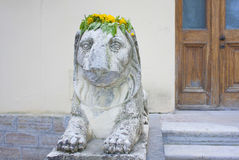 Stone lion a wreath of yellow flowers.Peterhof Russia Stock Images