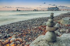 Stone man on the baltic sea with jetty in background stock photos