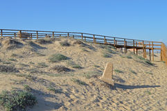 A Stone Marker Post On A Beach. An old marker post in front of a new walkway Royalty Free Stock Photos