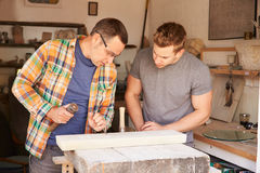 Stone Mason With Apprentice At Work On Carving In Studio Stock Images
