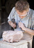 Stone Mason  sculpting  a slab of granite. Telford, England.- July 9th 2014:  Stone Mason  sculpting  a slab of granite. Dust, & stone fragments fly off into the Stock Images