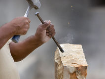Stone mason shaping block of stone. A stone mason shaping a block of stone with a chisel royalty free stock photos