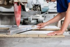 Stone mason woman measuring stone plate for sawing. In workshop Stock Photos