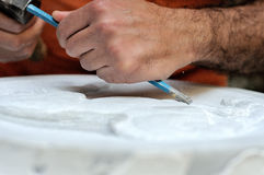 Stone mason at work carving an ornamental relief Stock Image