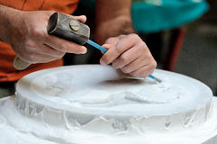 Stone mason at work carving an ornamental relief. (hand, hammer and chisel Stock Photo