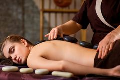 Stone massage back spa for a woman. Stone massage back spa for a women in the beauty center Stock Photos
