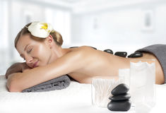 Stone massage. Beautiful woman getting hot stones massage in spa. Beauty treatments. Woman getting hot stone massage at spa salon Stock Photo