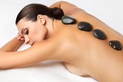 Stone Massage. Beautiful Woman Getting Spa Hot Stones Massage in Stock Photo