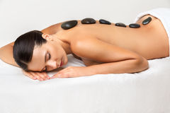 Stone Massage. Beautiful Woman Getting Spa Hot Stones Massage in Stock Photos
