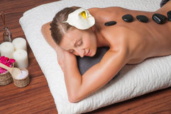 Stone massage. Beautiful woman getting spa hot stones massage in spa salon. Royalty Free Stock Photography