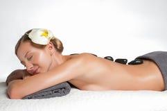Stone massage. Beautiful woman getting spa hot stones massage in spa salon. Stock Photos