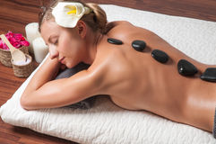 Stone massage. Beautiful womBeauty treatments, a woman relaxing at a health spa while having a hot stone treatment and massagean g Stock Photo