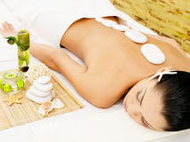 Stone massage for woman at  spa salon. Stone massage for young woman at beauty spa salon. Recreation therapy Stock Photo